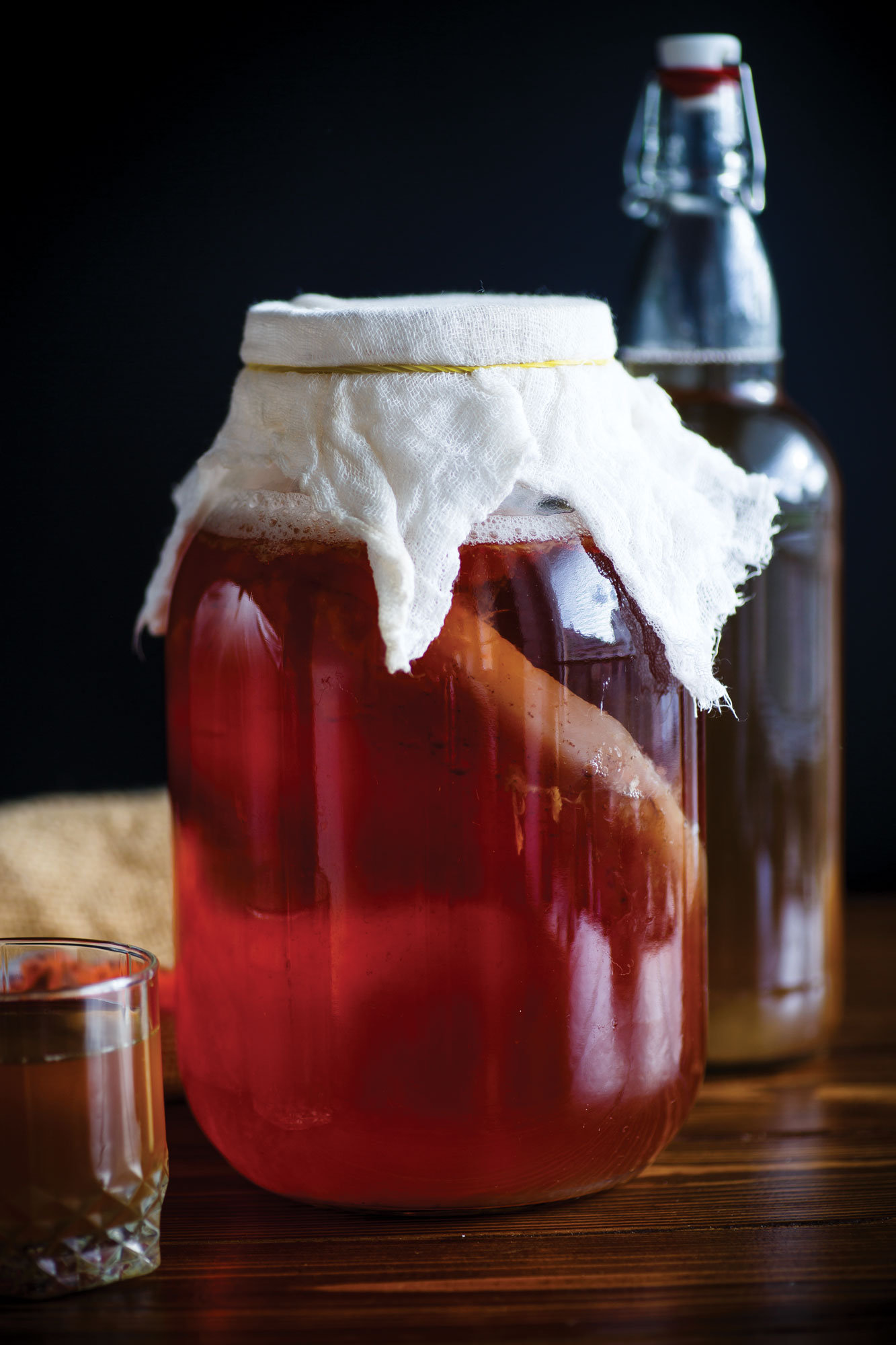 A jar of kombucha fermenting with a bottle in the background