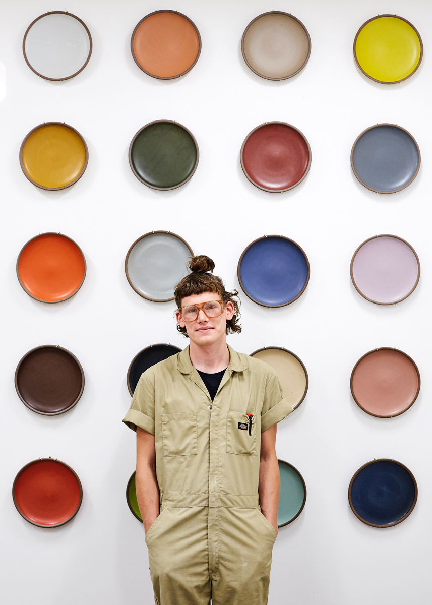 East Fork Pottery Kiln Lead Kyle Crowder standing in front of a wall of ceramic wares