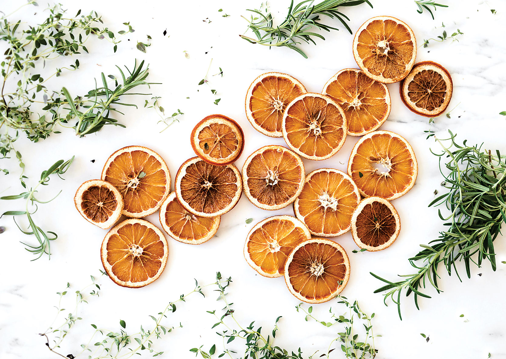 Dried orange slices and herbs spread on marble