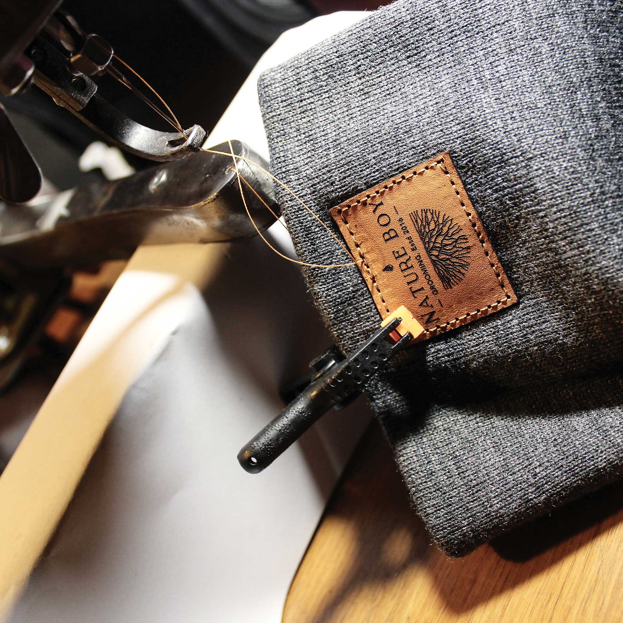 Leather tag being stitched onto a Nature Boy beanie