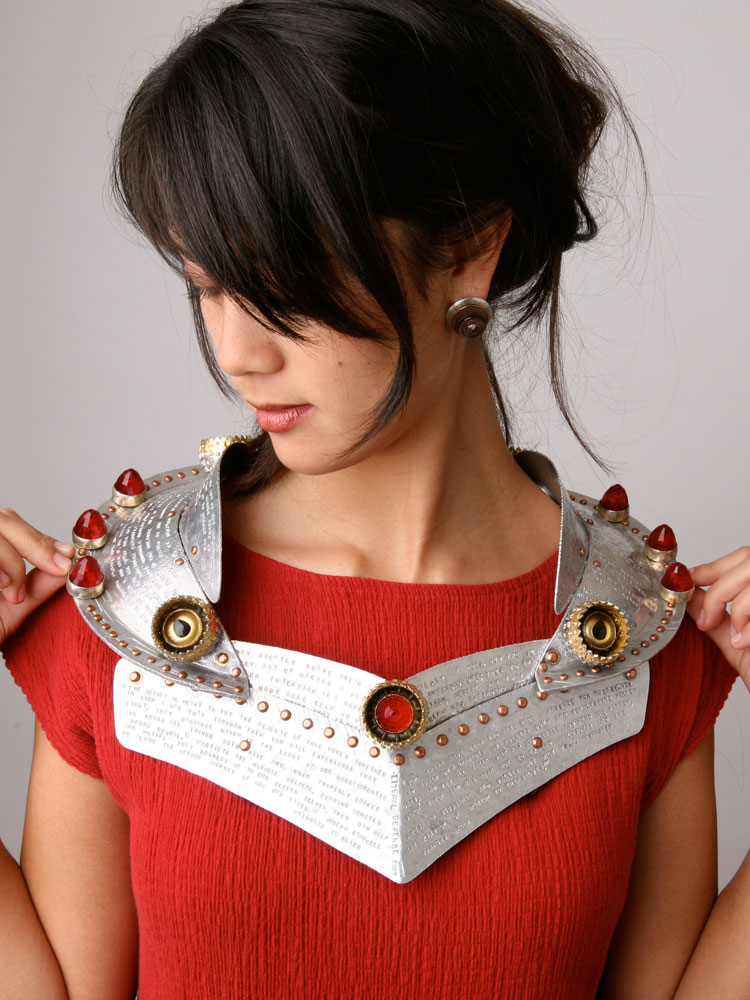 Person wearing ornate metal armor chest piece with lettering and red jewels
