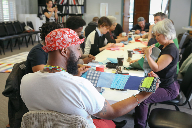 Community members help to stitch together sections of the quilt at a sewing bee.