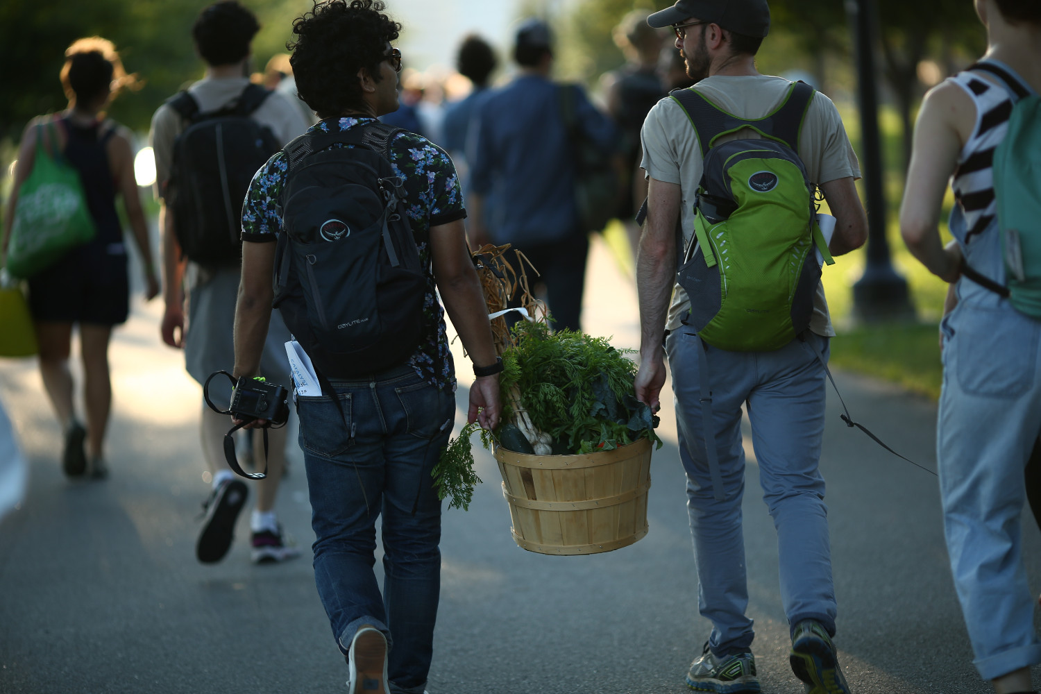 "Attendees carry food to the site of ""Then a Cunning Voice."""
