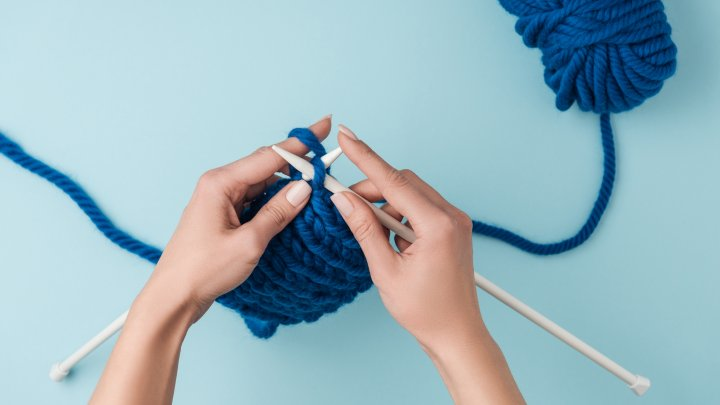 Hands knitting blue yarn