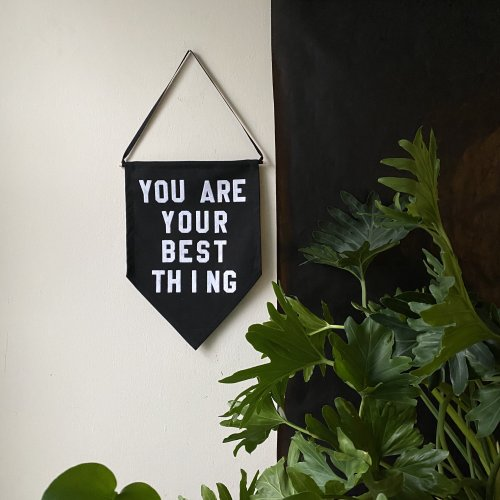 Black pennant with white lettering hanging on wall beside plant