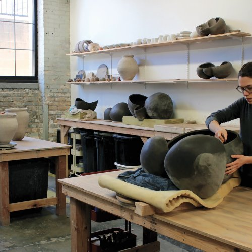 Two artists working on large ceramic vessels at respective tables in studio space with shelves